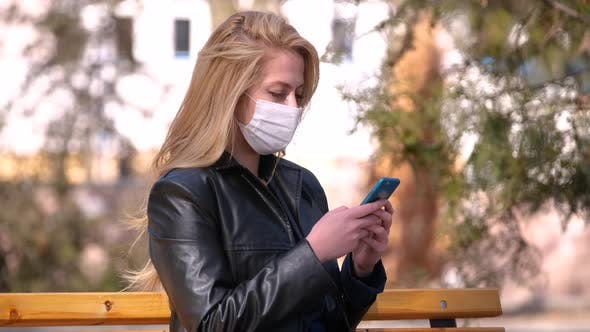 Woman In A Medical Mask Using Smartphone