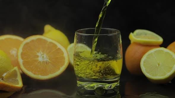 Thumbnail for Gießen Sie Saft in Glas-, Orangen- und Zitronenscheiben auf dem Hintergrund. Zeitlupe