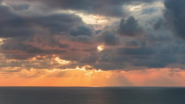 Thumbnail for Clouds Crossing the Sky Over the Sea Horizon at Sunset with Sun Rays Emerge Through the Storm Clouds