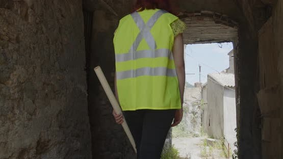 Young female architect or engineer walks down a street between abandoned houses