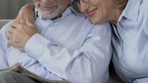 Adult Married Couple Reading Newspaper Embracing Together, Love and Respect