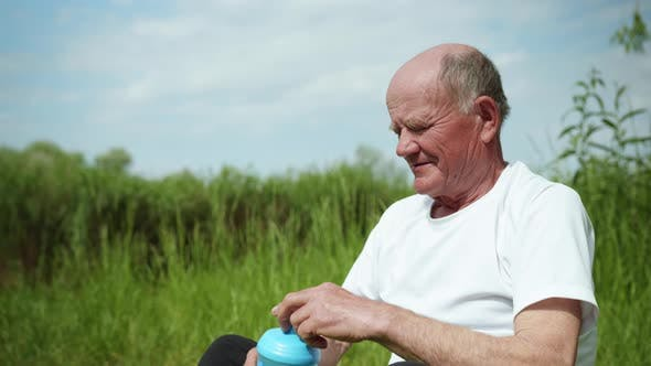 Thumbnail for Elderly Handsome Man Enjoys Life and Drinks Pure Healthy Water From Sports Bottle After Playing
