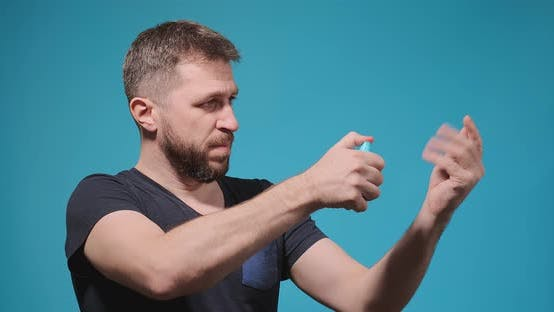 Muscular Man in Black Tshirt Sprays Antiseptic on Hands