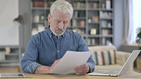 Old Man Reading Documents in Office