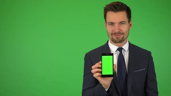 Thumbnail for A Young Businessman Shows a Smartphone with Green Screen To the Camera and Smiles - Green Screen