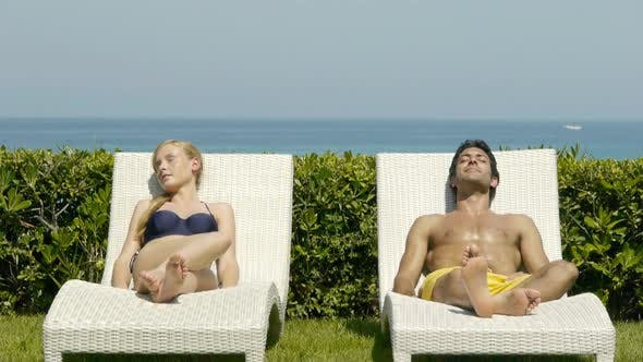 Thumbnail for Young couple on sun loungers holding hands