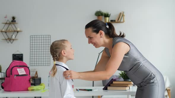 Mother Helping Pupil Girl Get Ready for School