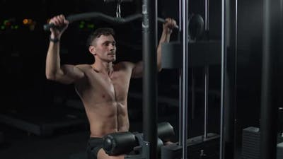 Athletic Man in the Gym Lifting Blocks on Rack Machine Training on Block Device and Gym Equipment