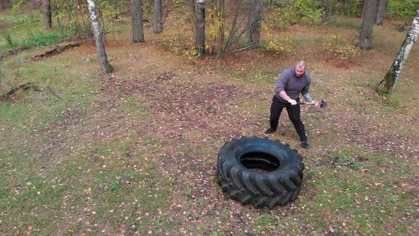 Thumbnail for Tough Man Bodybuilder Hitting the Truck Tire with a Heavy Iron Hammer - Tire Hammering