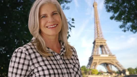 Woman smiles at camera with the Eiffel Tower in the background