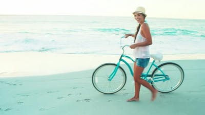 Happy woman walking on the beach with a bicycle