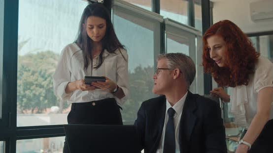 Thumbnail for Group of people discuss a project using a computer at workplace. Business meeting, Slow motion