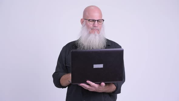 Thumbnail for Happy Mature Bald Bearded Man Using Laptop