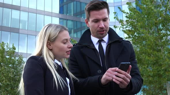 Thumbnail for A Businessman and a Businesswoman Work on a Smartphone and Talk - an Office Building in Background