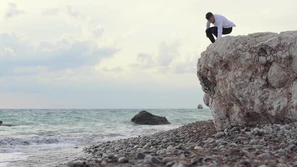 Thumbnail for Man Sitting on the High Hill of Rock and Enjoying Amazing View of Seaside