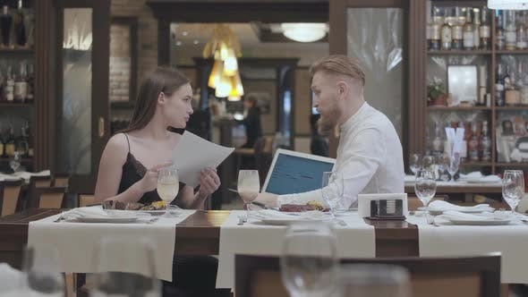 Thumbnail for Young Beautiful Woman Sit with Papers on the Table in Restaurant with a Mature Bearded Man