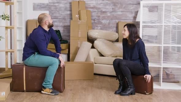 Thumbnail for Couple Talking and Sitting on Suitcases After Carrying Boxes