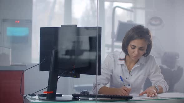 Thumbnail for Female Doctor Writes a Prescription Fills Out Medical History at a Desk in a Medical Office