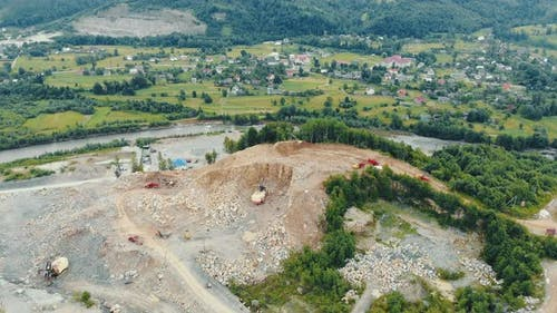 Flight Over a Quarry in the Mountains Where Stones and Other Rocks Are Mined. Heavy Machinery