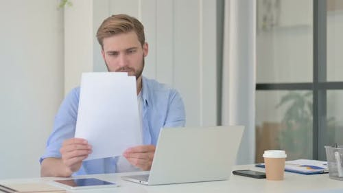 Creative Man with Laptop Reading Documents in Office