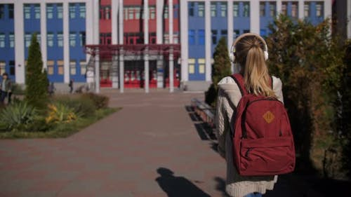 Adorable Schoolgirl Walking Towards School Building