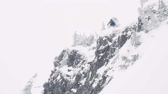 Thumbnail for Snowboarder Lands Dangerous Big Air Trick off Large Rock Riding Away Through Winter Powder Snow