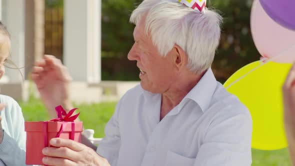 Thumbnail for Happy Grandfather Receiving Birthday Gift from Family on Outdoor Celebration