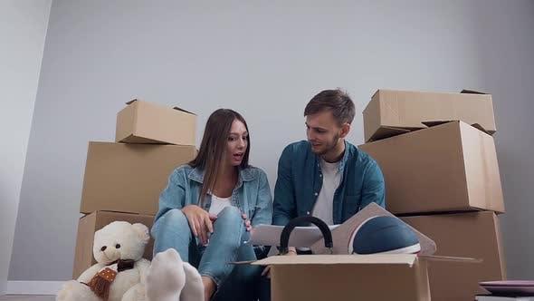 Glücklicher Mann und Frau in stilvollen Kleidern sitzen auf dem Parkett
