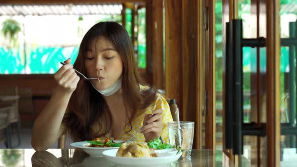 young woman with face mask eating spaghetti food in restaurant, New normal concept