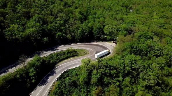 Thumbnail for FPV Semi Truck Driving Along Mountain Road Going Through Forest Landscape