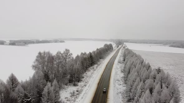 Aerial Footage Flying Over a Winter Route in the Middle of Snowcovered Trees
