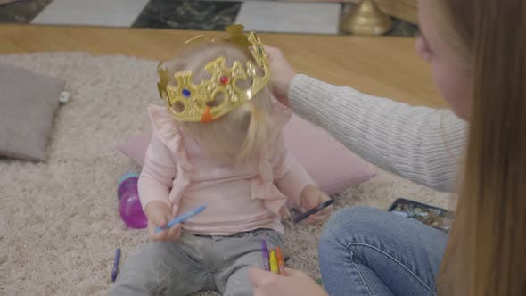 Cover Image for Close-up of Young Caucasian Mother Trying To Put Toy Crown on Daughter's Head