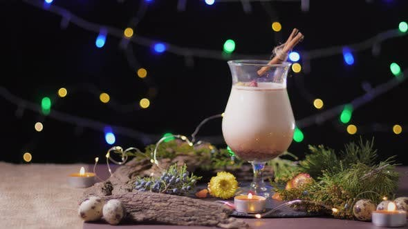 Season Eggnog, Handsome Cocktail Glass with Traditional Egg Drink on Decorated with Christmas Tree