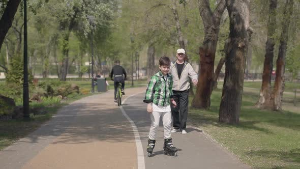 Thumbnail for Cute Boy in Bright Clothes Rollerblading in the Park, His Grandfather Walking Near