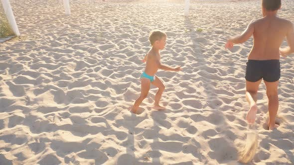 Happy Children Run on the White Sand of the Beach in the Setting Sun