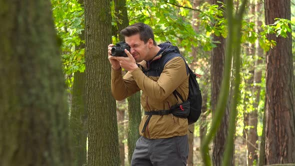 Thumbnail for A Hiker Takes Pictures with a Camera in a Forest