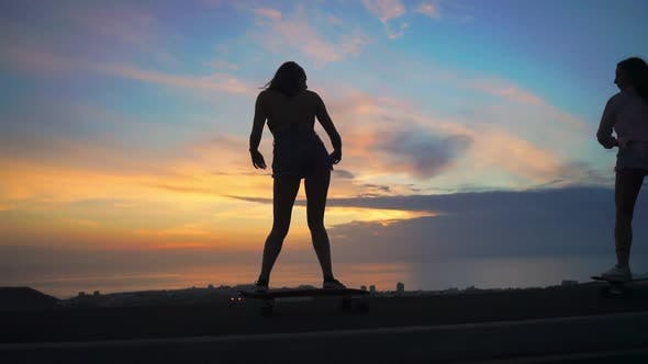 Thumbnail for Skateboarding Silhouette of Two Girls Against the Sky and the Sun