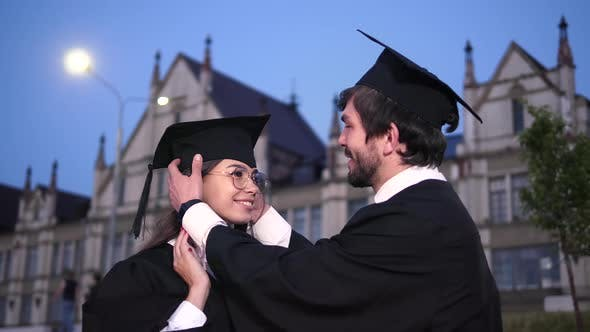 Thumbnail for Two Happy Graduating Students. Male Graduate Student Helps the Girl To Straighten the Cap
