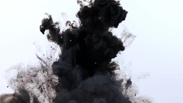 Black paint sprayed into water with orange following