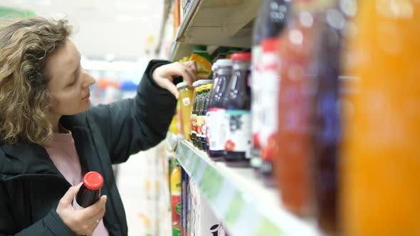 Thumbnail for Woman In Supermarket Choosing Juice In Bottle