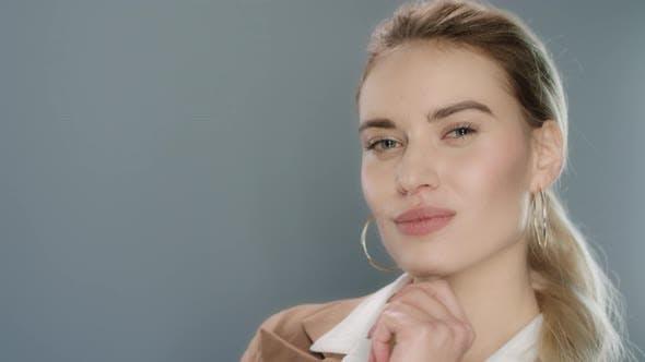 Thumbnail for Sinnliche Frau posiert und zwinkend zu Kamera in grau Studio Hintergrund