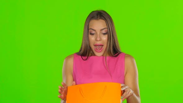 Thumbnail for Woman Looks at the Package and Consider Buying. Green Screen. Close Up