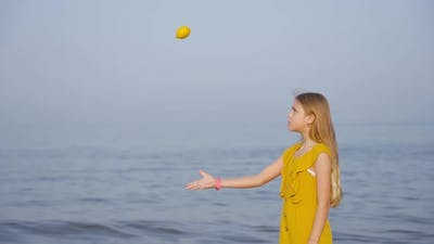 Teen Throws a Lemon in Slow Motion in Front of the Sea