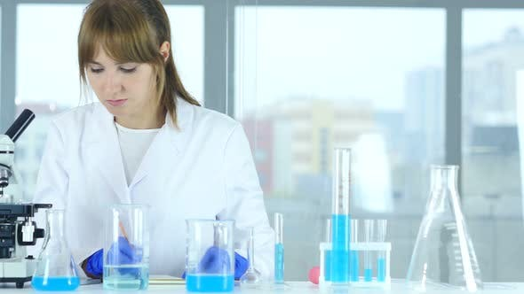 Thumbnail for Female Scientist in Laboratory Reading Documents