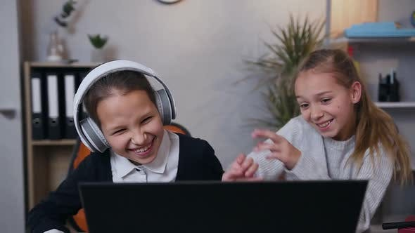 Teenage Girls Fooling Around in Front of Computer During Playing Video Game