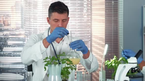 In a Chemistry Laboratory Research Scientist Mixing Two Compounds in Flask Using Pipette