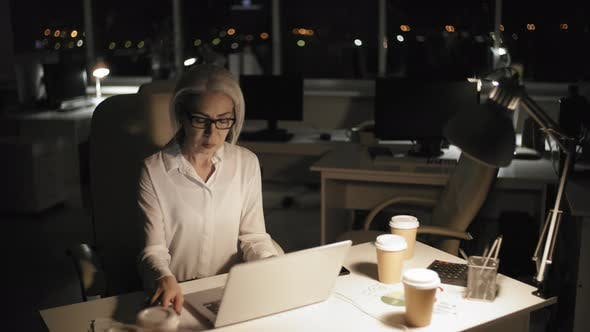 Thumbnail for Stressed Grey-Haired Career Woman Working in Office at Night