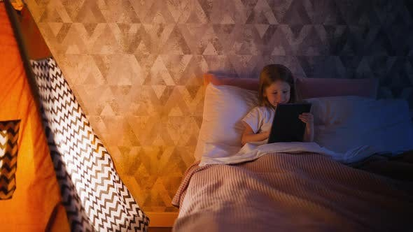 Happy Little Girl Plays on Tablet in Bed By Children Tent