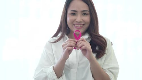 World breast cancer day concept, young Asian woman smiling and holding pink ribbon on hand