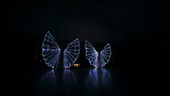 The Girls Perform a Dance with LED Wings. LED Lights Glow in the Dark. Young Girls Revolve Around